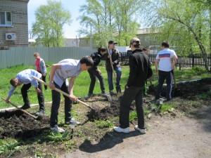 Школьники помогают вскопать грядки для посадки цветов